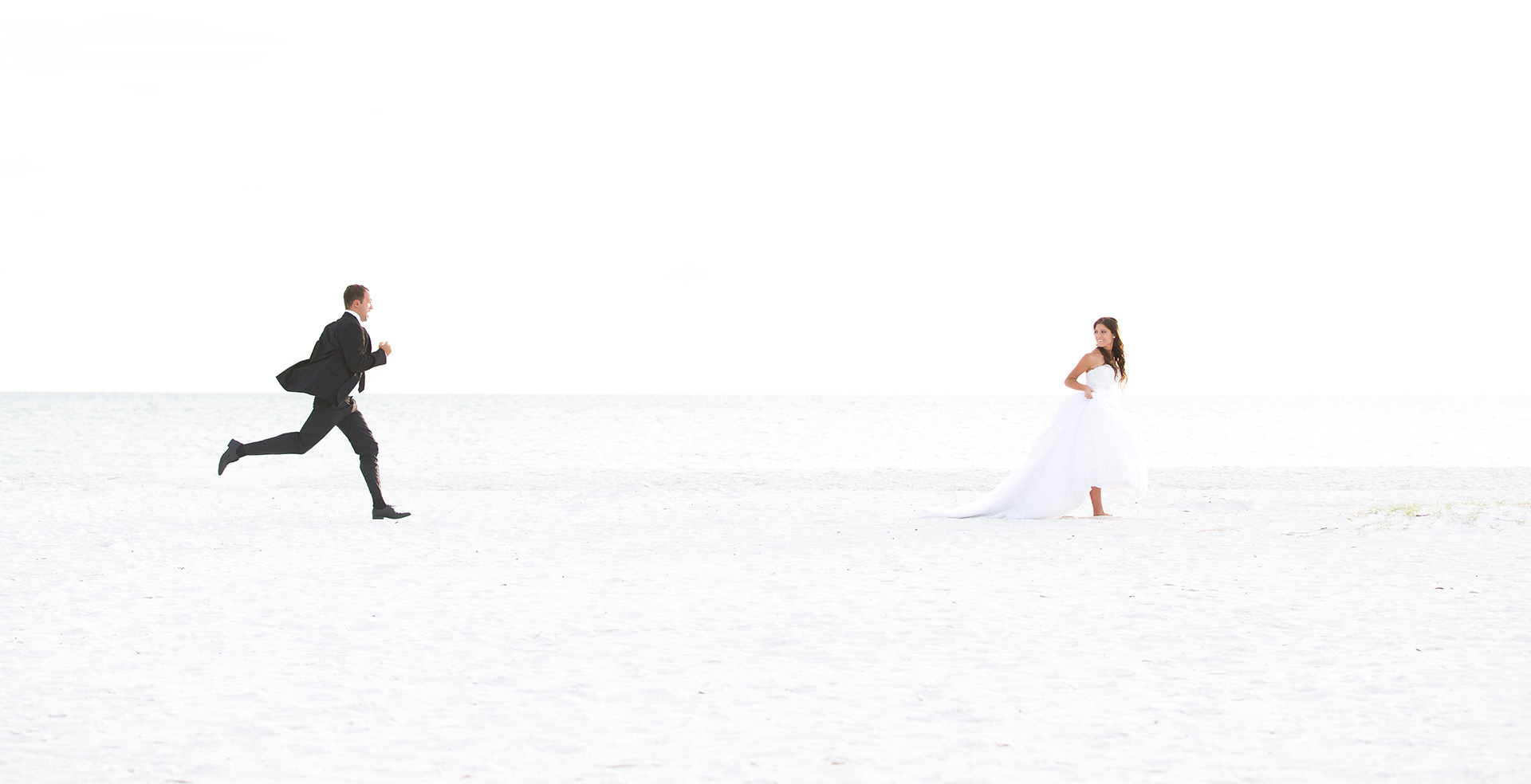 married couple chasing each other on beach